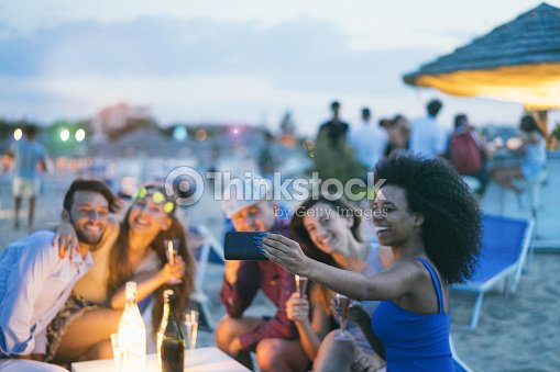 Happy friends taking selfie with smartphone at beach party outdoor - Young people having fun together at kiosk bar drinking champagne  - Focus on african girl hand phone- Youth and summer concept : Stock Photo