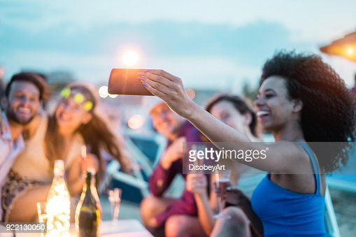 幸せのお友達が楽しんで飲むバーのシャンパン キオスク - モバイル携帯電話にソフト フォーカス - 若者のライフ スタイルと休暇コンセプトで若い人たちのビーチ パーティー - 屋外でスマート フォンと selfie を引き継ぐ : ストックフォト