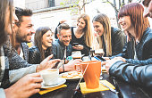 Happy friends talking and having fun with mobile smart phones at restaurant drinking cappuccino and hot tea - Young people together at cafeteria - Friendship concept with men and women at coffee bar