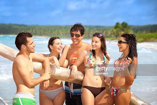 Heureux amis discutant sur une plage tropicale turquoise