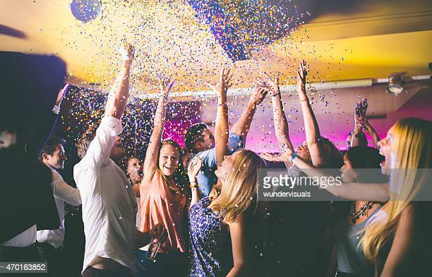 Happy friends throwing confetti into the air at a celebration