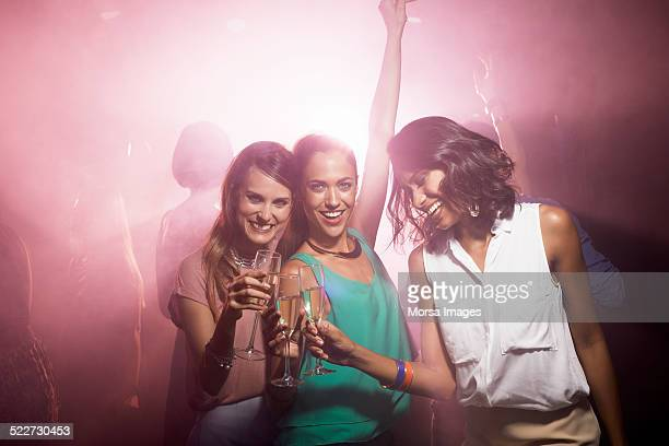 Happy friends toasting champagne at nightclub