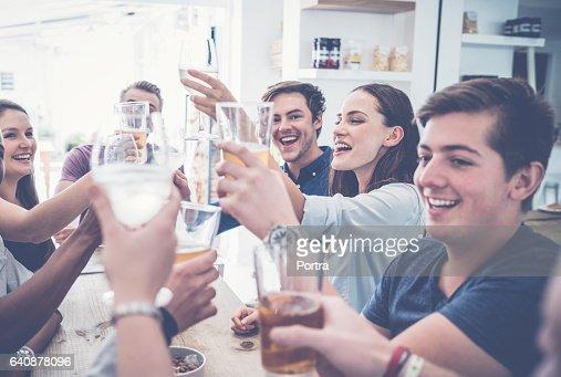 Happy friends toasting drinks in restaurant