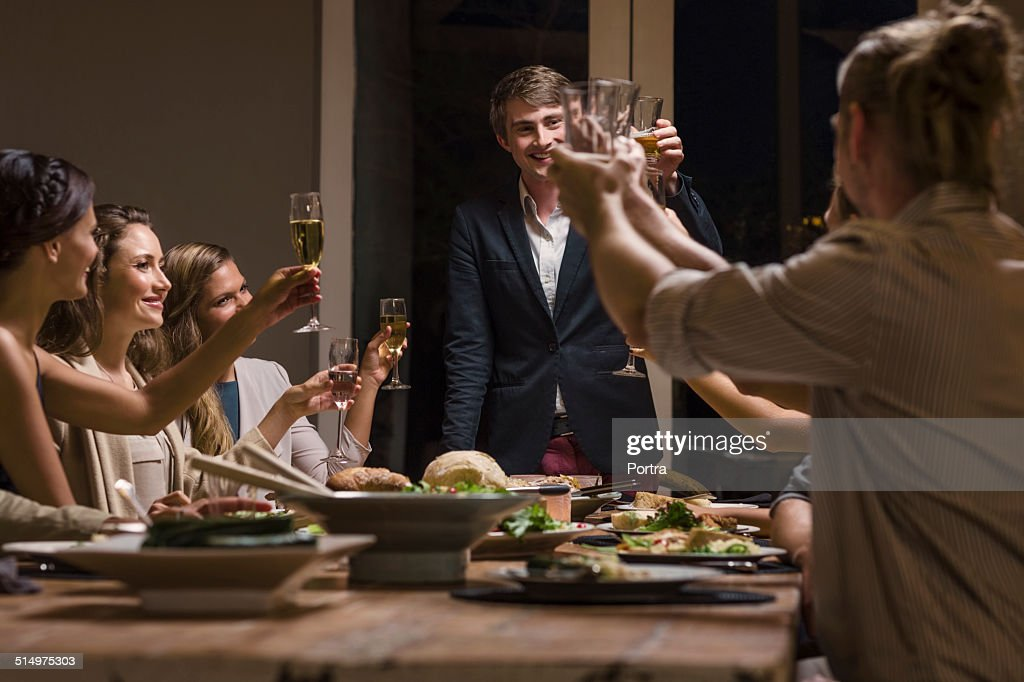 Happy friends toasting wineglasses at dinner table