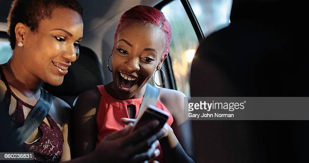 Happy friends using car share app in taxi