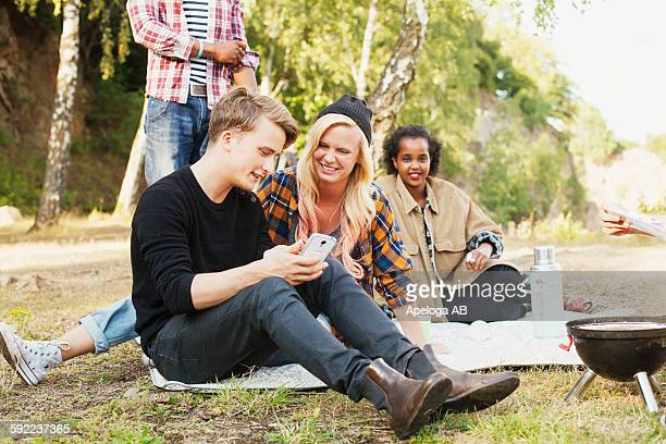 Happy friends using mobile phone together during picnic