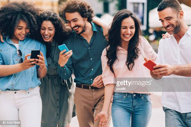 Happy friends using smart phones