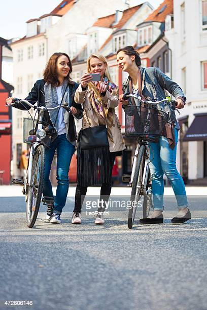 Happy friends walking in the city looking on mobile phone