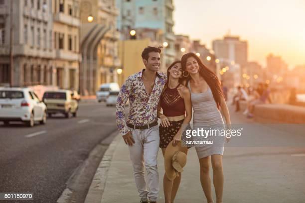 Glückliche Freunde gehen auf Bürgersteig während des Sonnenuntergangs