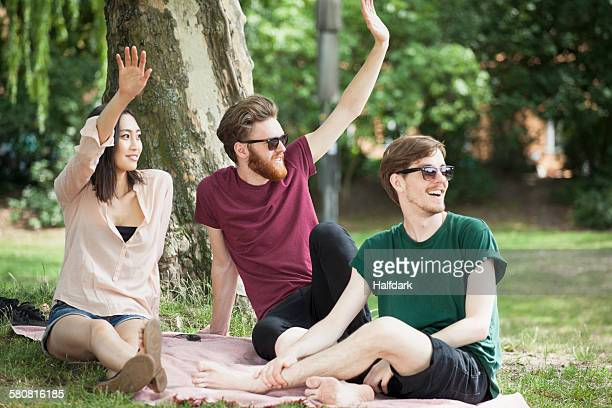 Happy friends waving while relaxing at park