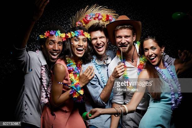 Happy friends wearing garlands in nightclub