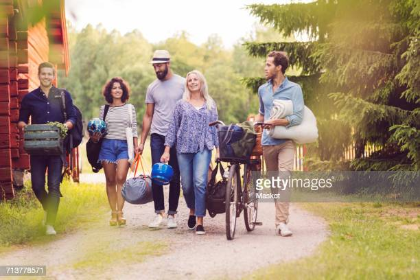 Happy friends with bicycle and luggage walking on pathway by cottage