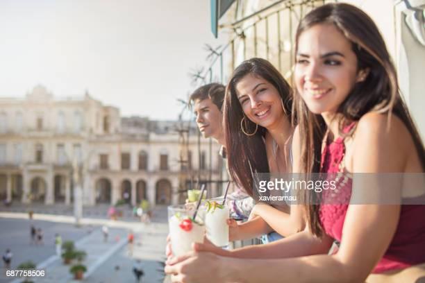 Gelukkige vrienden met dranken op balkon op zonnige dag