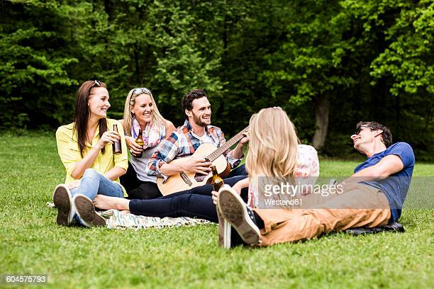 Happy friends with guitar and beer bottles relaxing in park
