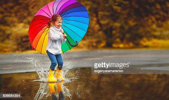 Chica de niño divertido feliz con paraguas saltando sobre los charcos en botas de goma : Foto de stock