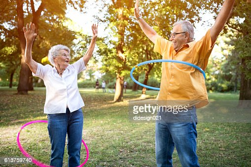 Happy funny senior couple playing hulahop in park : Foto de stock
