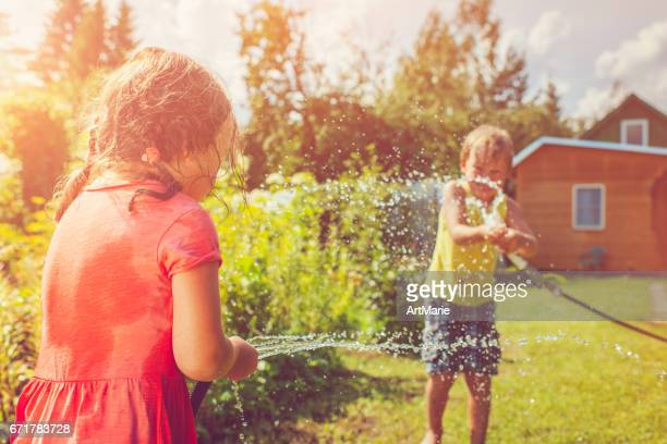 Happy girl and boy playing with sprinkler