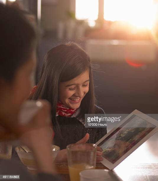 Happy girl at breakfast table with tablet computer