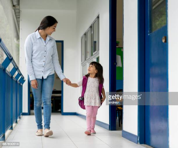Happy girl at school holding the hand of her teacher