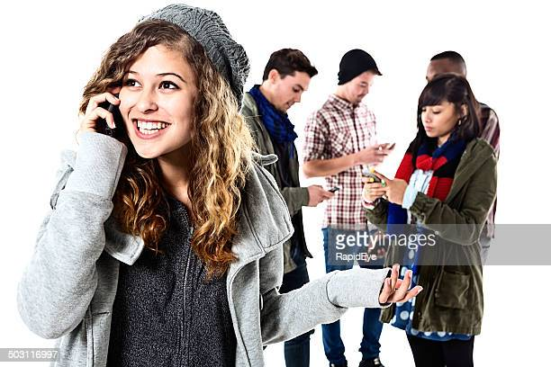 Happy girl chats on cellphone, friends in background