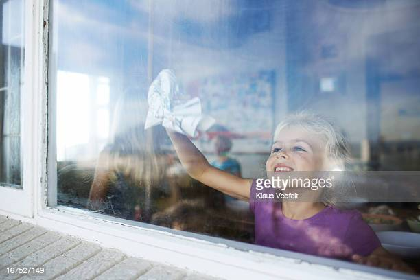 Happy girl cleaning window