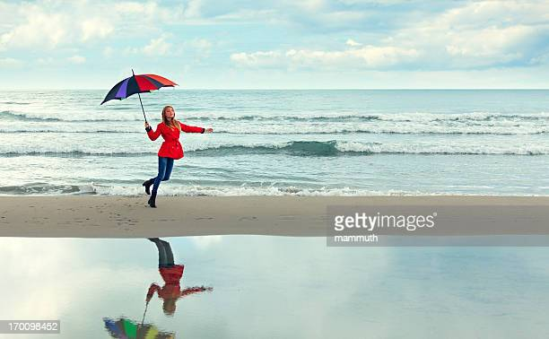 happy girl dancing with an umbrella at the sea
