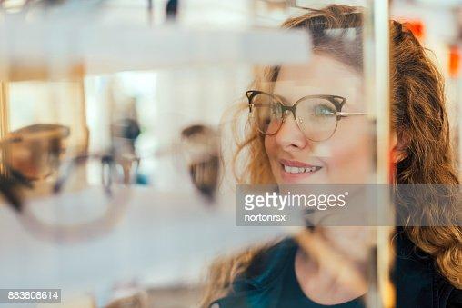 Happy girl deciding to buy new glasses. : Stock Photo