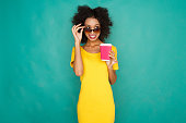 Curly smiling mulatto girl in bright yellow dress and sunglasses with take away coffee cup. Young woman at azur studio background looking cunningly from under her dark glasses, copy space
