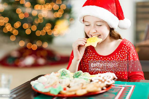 Happy Girl Eating Christmas Cookies in front of Tree Close-up