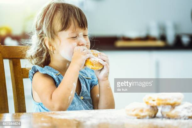 Happy girl eating delicious donut