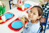 Pretty Asian girl sitting at table with classmates in primary school canteen, eating sandwich and smiling at camera cheerfully