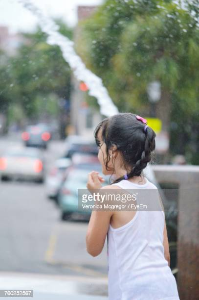 Happy Girl Enjoying In Spraying Water On Road