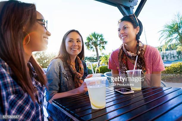 Happy girl amis d'avoir boissons au patio du restaurant