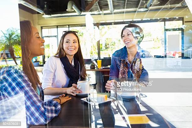 Happy girl friends having lunch together in coffee shop