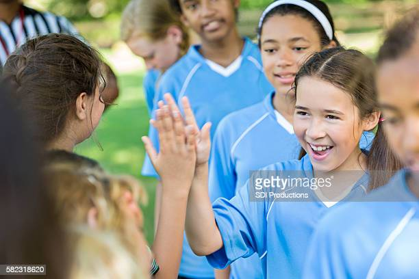 Happy girl giving other team high fives after good game