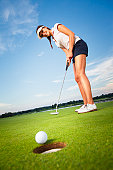 Smiling woman golf player putting successfully ball on green, ball dropping into cup, blue sky in background.