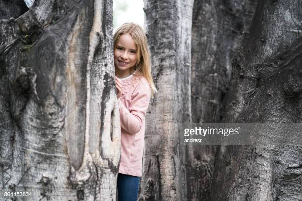 Happy girl hiding behind a tree at the park