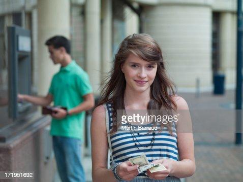 Happy girl holding money near ATM machine