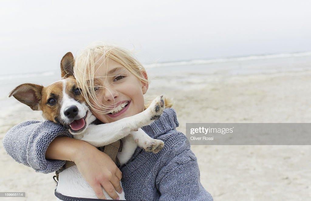 Happy girl hugging dog on the beach, portrait : Stock Photo