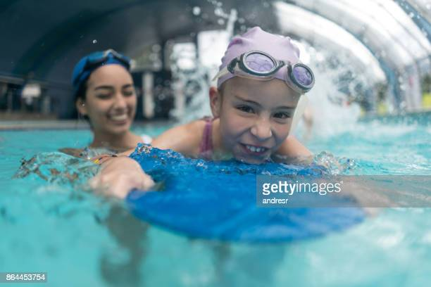 Happy girl in a swimming class with a teacher