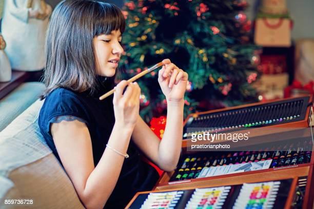 Chica feliz está examinando su Navidad regalo/dibujo conjunto
