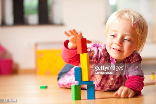 happy girl is playing with blocks