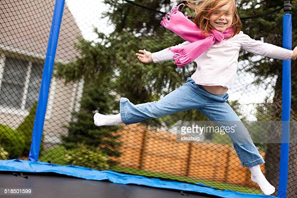 Happy Girl Jumping Outdoors on Trampoline