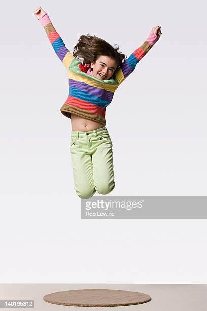 Happy girl (8-9) jumping, studio shot