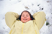 Happy girl lying down in the snow