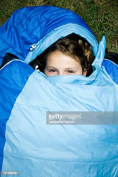 Happy girl lying in sleeping bag