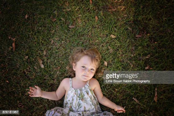 Happy Girl Lying on the Grass Arms Outstretched