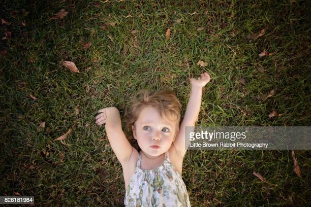 Happy Girl Lying on the Grass With Arms Up Pursed Lips
