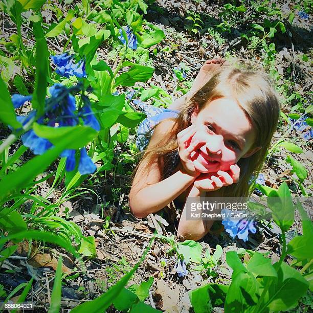 Happy Girl Lying With Hands On Chin By Blue Flowers On Field