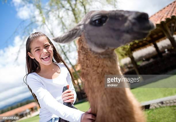 Glückliche Mädchen auf einem Lama